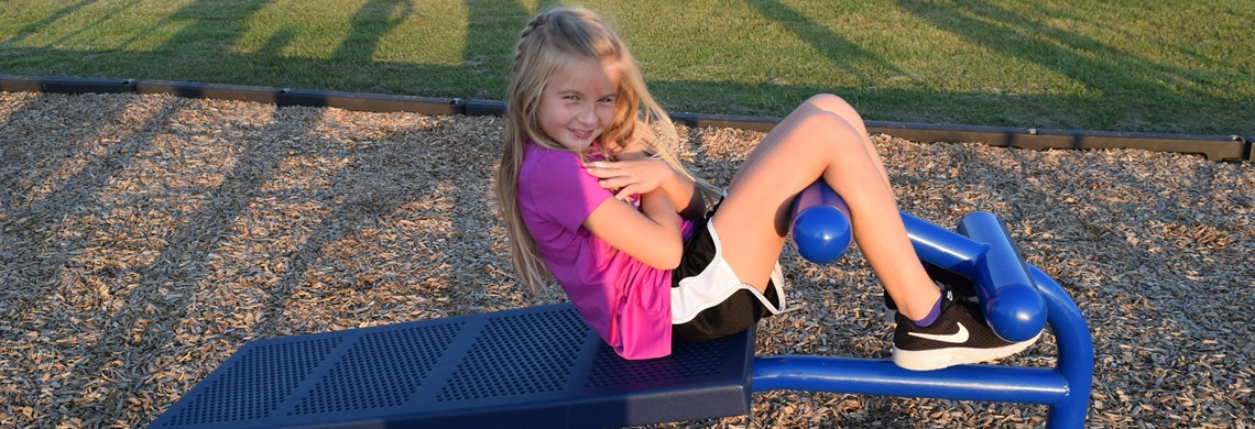 Ava using the fitness equipment on the playground